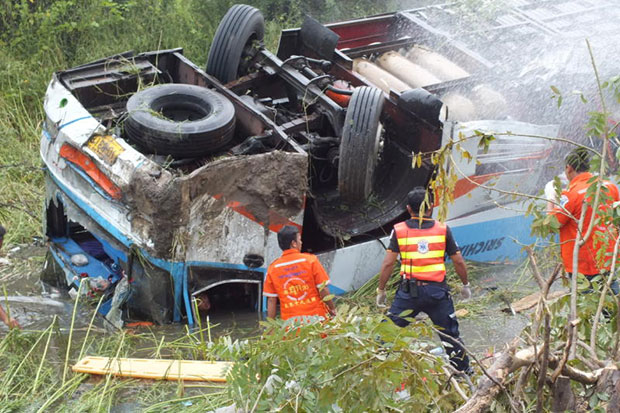 Rescue workers try to reach passengers trapped inside an overturned double-decker tour bus in Nakhon Ratchasima. Three people were killed in the accident and 20 injured. (Bangkok Post file photo)