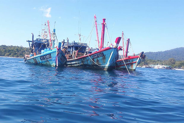 Three Malaysian-flagged fishing vessels spotted fishing illegally in Thai waters off Satun on Jan 7 are seized and 12 Thai men on board, including three skippers and nine crew members arrested. (Photo by Achadtaya Chuenniran)