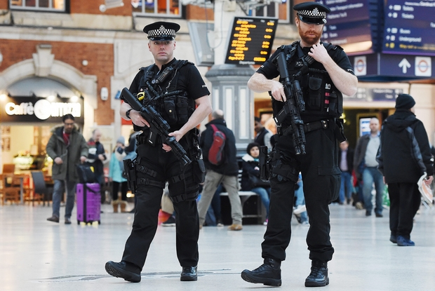 Armed police patrol a train station in London on Friday. Armed patrols have become routine in Britain, where most police do not carry guns, since the terror attacks in Paris. (EPA Photo)