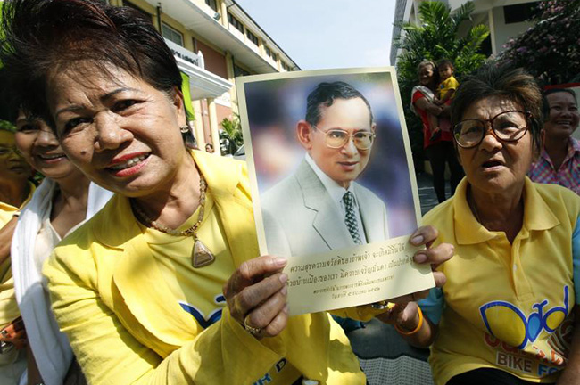 Well-wishers hold a photograph of King Bhumibol Adulyadej as they wait for the King's departure at Siriraj Hospital in Bangkok Jan 11. (EPA photo)