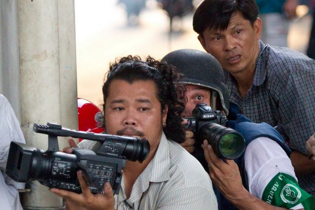 Journalists seek cover but continue working during the 2010 street protests and battles. (AP photo)