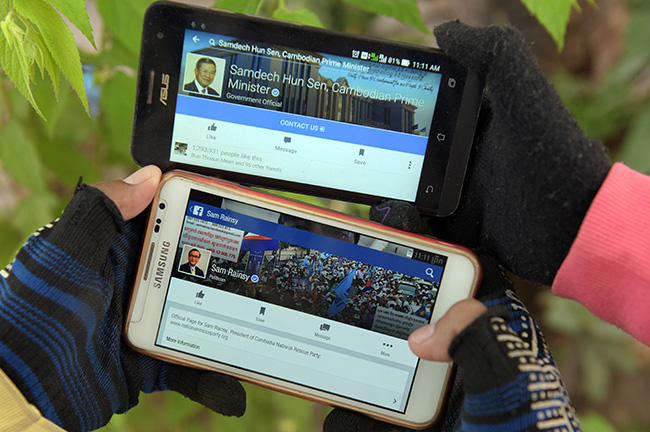 Cambodian people hold their mobile phones displaying Facebook pages of Cambodian Prime Minister Hun Sen (top) and the opposition party leader Sam Rainsy (below) in Phnom Penh on Jan 8. (AFP photo)