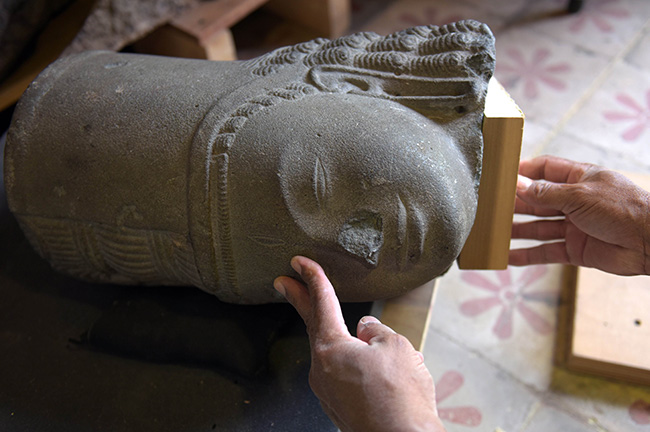 A Cambodian museum employee attaches a wooden block to the head of the Harihara statue at the national museum in Phnom Penh on Jan 19. A French museum has returned the statue head of a Hindu god that was ransacked from a Cambodian temple 130 years ago. (AFP photo)