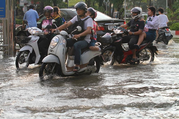 Motorcyclists pass through the flooded Thippawan housing estate on Soi Thippawan 41, off Theparak Road, in Samut Prakan after heavy rain in Bangkok and surrounding areas on Wednesday morning. (Photo by Somchai Poomlard).