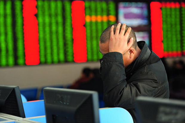 A Chinese investor looks at a computer screen showing stock information at a brokerage house in Fuyang, Anhui province, on Thursday. (Reuters photo)