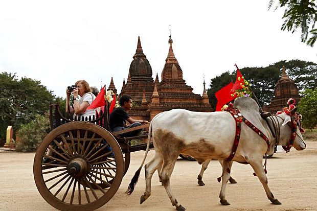 Foreign tourists sit on a bullock cart riding by a coachman during their sightseeing in Bagan city, Myanmar, on Nov 11, 2015. (EPA photo)
