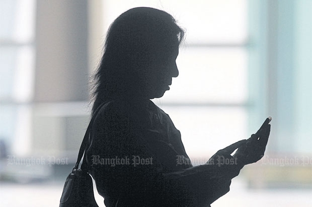 A woman uses her smartphone while waiting for service at a Bangkok bank. A survey reveals rising smartphone data consumption in Thailand.SEKSAN ROJJANAMETAKUN