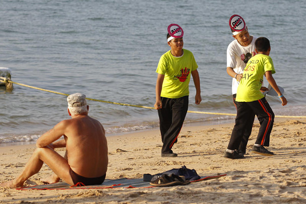 Students play near a tourist as they wear headbands to raise awareness on World Aids Day in Pattaya on Dec 1. The resort city is a main stop for visitors from Russia. (Reuters photo)