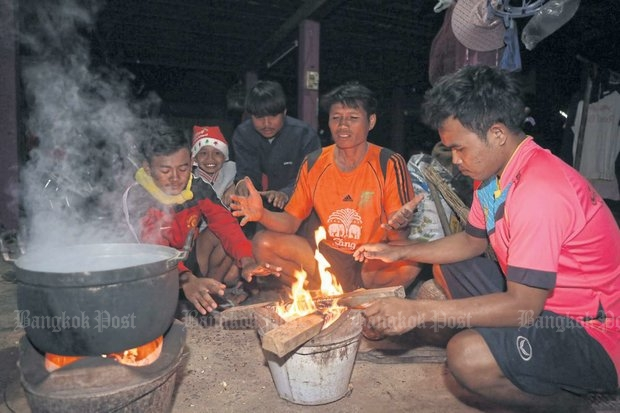 Villagers at Sai Yong village in Buri Ram's Muang district sit around a fire to warm themselves up Sunday night after a cold front dropped temperatures over the North and Northeast. (Photo by Pattarapong Chatpattarasill)