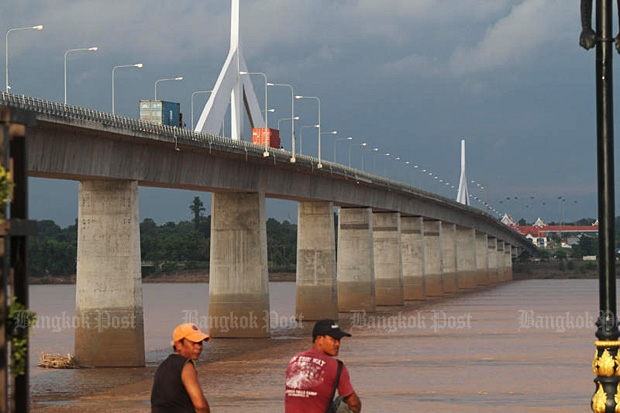 Two men sit on the bank of the Mekong River near the Thai-Lao Friendship Bridge in Muang district in Mukdahan on Aug 31. (Bangkok Post photo)