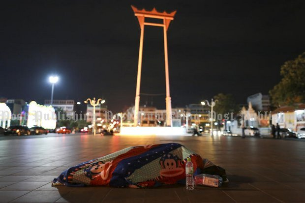 A homeless man retreats deeply into his thin blanket in front of Bangkok City Hall. Temperatures in the capital on Wednesday should be between 13-16C. (Photo by Patipat Janthong)