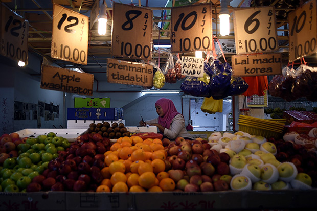 A Malaysian Muslim woman waits for customers at her fruit stall at a wet market in Kuala Lumpur on Jan 28. Malaysia on Thursday trimmed its 2016 growth forecast and said it would cut spending as slumping global oil prices squeeze the economy. (AFP photo)
