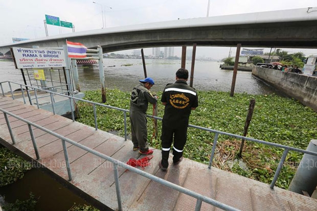 Rescue workers try to collect a piece of body part found in the river on Tuesday. (Bangkok Post file photo)