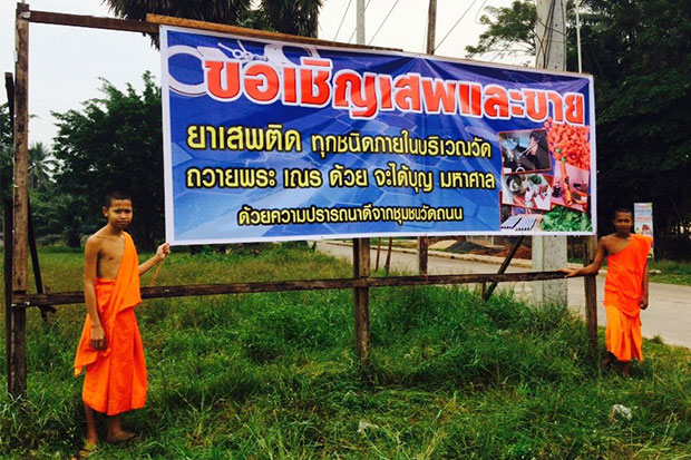 Two novices stand near the large banner put up by the angry abbot of Wat Thanon Suwanprasit in Surat Thani, sarcastically inviting everyone to take and sell illicit drugs inside the temple. (Photo by Supapong Chaolan)