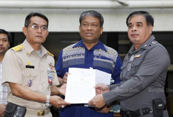 Pol Lt Col Jan Chaisawasdi (right) files his letter complaining about the prime minister's order scrapping the position of official interrogator to a government official at the complaints centre on Monday. The two were flanked by former Democrat Party MP for Bangkok Watchara Petchthong. (Photo by Thanarak Khunton)
