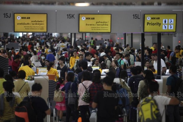 Nok Air check-in counters were packed at Don Mueang airport Monday after a wildcat walking by pilots forced cancellation of nine flights on Sunday. (Photos by Thiti Wannamontha)