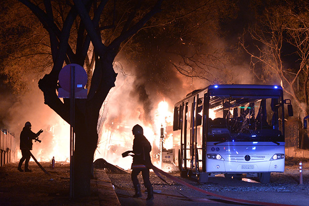 Firefighters try to extinguish the flames at the scene of a car bomb detonation close to buildings of the Turkish military, in Ankara Feb 17. Twenty-eight people were killed in the attack. (EPA photo)