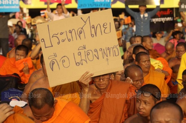 A monk carries a homemade sign that reads, 'Thailand is a Buddhist country'. He was involved in the protest last week to pressure the government to endorse the Sangha Council's nomination of the next supreme patriarch, and to make Buddhism the official state religion. (Photo by Pornprom Satrabhaya)