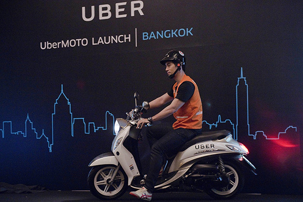 A man drives a motorbike onto a stage during the launch of UberMoto at a hotel in Bangkok on Feb 24. Uber offered its first motorbike taxi service, launching a pilot scheme in Bangkok which could spread across Asia as it takes on chief regional rival Grab Taxi. (AFP photo)