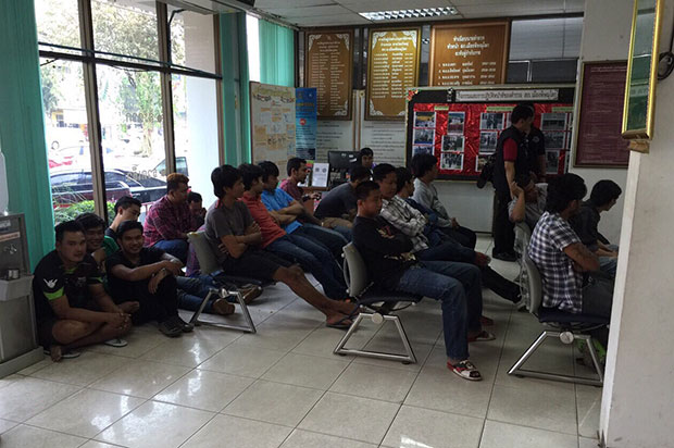 Loan-sharking suspects sit at Phitsanulok police station waiting to acknowledge charges. (Photo by Chinnawat Singha)