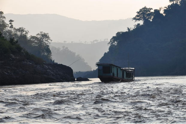 A boat makes its  way down the  Mekong River  near the proposed  Pak Beng Dam  site, downstream  of Chiang Khong  district, Chiang Rai.  Dam building on  the lower Mekong  is accelerating,  and it threatens  to leave a path of  destruction in its  wake. Pianporn  Deetes