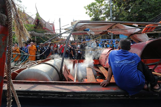 A taxi boat driver looks on as police officers and officials inspect a boat after its engine exploded at the Wat Thep Leela pier on Saturday. (EPA photo)