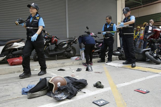 Detectives and forensic investigators tried to piece together what happened during last Friday's failed and fatal robbery of a Bangkok gun shop. (AP photo)