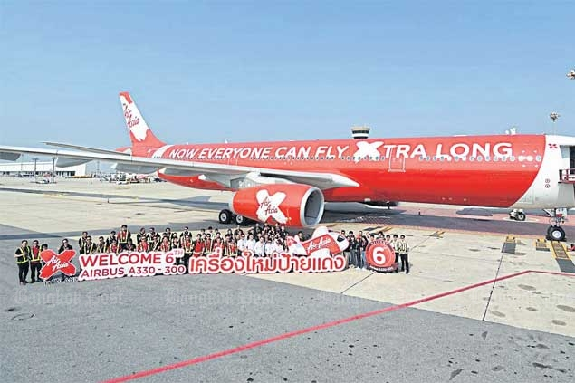 Thai AirAsia X staff celebrate the arrival of the long-haul low-cost carrier's sixth Airbus 330-300 at Don Mueang airport yesterday. Low-cost carriers are increasingly the choice for local flyers.