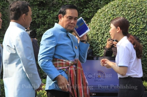 Prime Minister Prayut Chan-o-cha yesterday listens to an English lesson through Echo English, an app for Thais learning English with native speakers. THANARAK KHUNTON