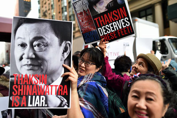Thais and Thai-Americans hoist placards in New York to protest against the presence of former premier Thaksin Shinawatra at a private club where he spoke on Wednesday, March 9. (AFP photo)