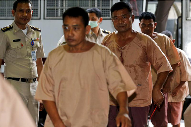 Lt Gen Manas Kongpan, a suspected human trafficker, is escorted by officers as he arrives for a hearing at the criminal court in Bangkok on Tuesday. (Reuters photo)