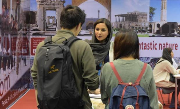 This photo taken on March 10, 2016 shows a woman chatting with visitors at the booth of Iran at the International Tourism Fair ITB in Berlin.(AFP photo)