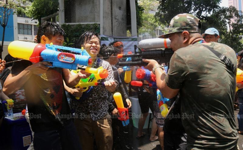 People shoot water at each other on Silom Road, Bangkok, in last year's Songkran. (Photo by Narupon Hinshiranan)