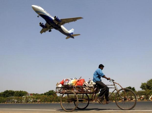 An IndiGo Airlines aircraft flies overheadas a man pedalsa cycle rickshaw in Ahmedabad, India.