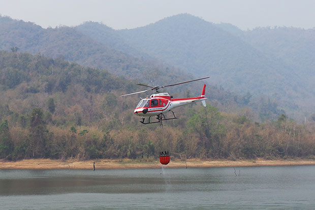 A helicopter scoops water from Huay Pa Lao reservoir to dump on the fire burning in Pa La-oo Noi forest, part of Kaeng Krachan National Park. (Photo by Chaiwat Satyaem)