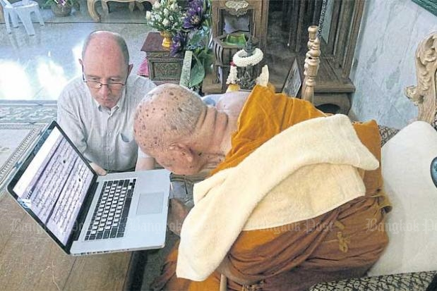 Monk reads palm leaf manuscript on the manuscript website.