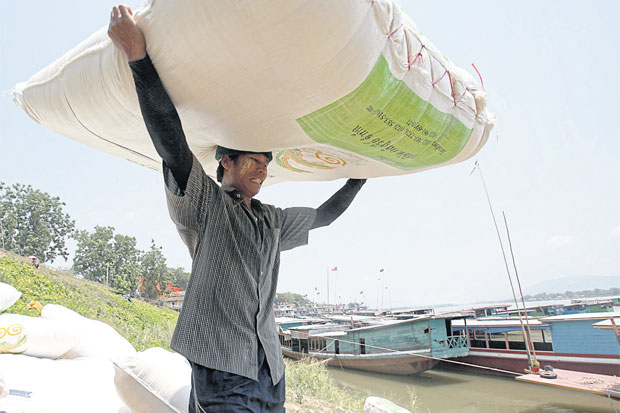 A worker hauls cargo to a docking vessel at a Mekong River pier in Chiang Rai province. Japan will finance a programme to improve human resources and labour in the Greater Mekong Subregion. PATTARAPONG CHATPATTARASILL