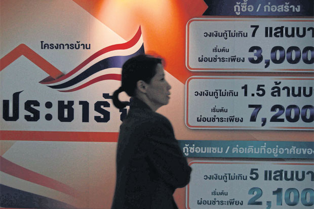 A woman walks past an ad board at GH Bank's headquarters promoting loans for the Pracha Rat low-cost housing project. SOMCHAI POOMLARD