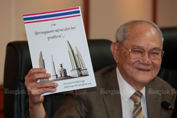 CDC chairman Meechai Ruchupan holds a copy of the draft charter at a news conference on Tuesday. (Photo by Chanat Katanyu)