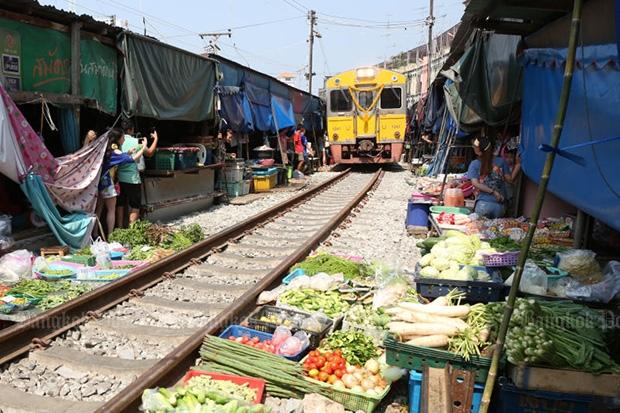 A train slowly makes its way through the folding umbrella market in Samut Songkram on Friday. (Photo by Pattarapong Chatpatarasill)