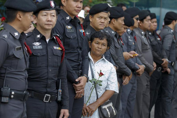 A supporter with a red rose stands among policemen, while waiting for ousted former prime minister Yingluck Shinawatra to arrive at the Supreme Court on Friday. (Reuters photo)