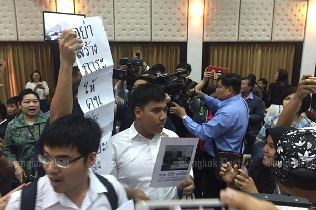 Student activist Siriwith Serithiwat (centre) protest Constitution Drafting Committee chairman Meechai Rechupan during his address on the draft charter at Thammasat University's Rangsit campus on Tuesday. (Post Today photo)