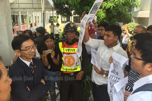 Students demonstrate against the draft charter in the presence of university rector Somkit Lertpaithoon, left, at Thammasat University's Rangsit campus in Pathum Thani province on Tuesday. (Photo by Chairat Patcharatrirat)