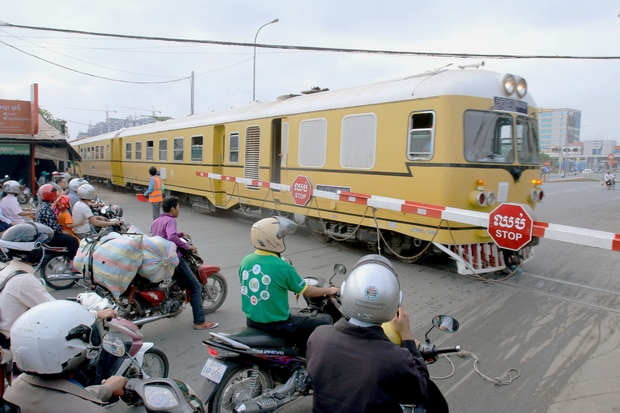 Motorcyclists wait while a Royal Railways of Cambodia passenger train moves through a crossing in Phnom Penh en route to Sihanoukville on Saturday. (Kyodo photo)