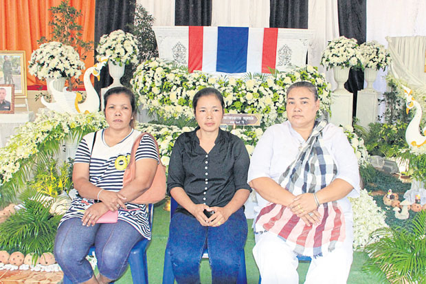 Beating victim Songtham Mudmad's mother (centre) and relatives sit in front of his coffin. His mother has asked Prime Minister Prayut Chan-o-cha for justice and refused to give permission to cremate her son's body until her voice is heard.