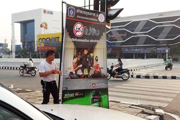 A police officer moves one of the controversial signboards from a sidewalk in Chiang Mai's Muang district on Sunday. (Photo taken from Facebook of 