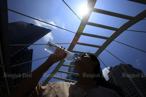 A young woman drinks water amid the stifling April summer heat. The Meteorological Department predicts Songkran temperatures in the North and Central Pains this year can hit a near-record 44.5. (Bangkok Post file photo)