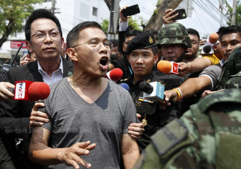 Watana Muangsook protests his innocence as he is escorted by soldiers to the 11th Military Circle in Dusit district Monday. (Thanarak Khunton)