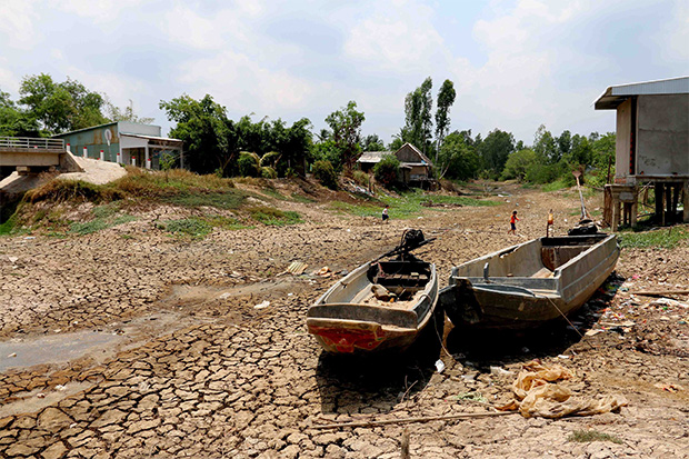 Two boats lie on cracked ground in a dry area in Ca Mau province, Vietnam, April 18. Vietnam is facing the most serious drought in the last 90 years, according to a statement by the Ministry of Agriculture and Rural Development. Around 340,000 families have faced water shortages caused by the drought, according to media reports. (EPA photo)