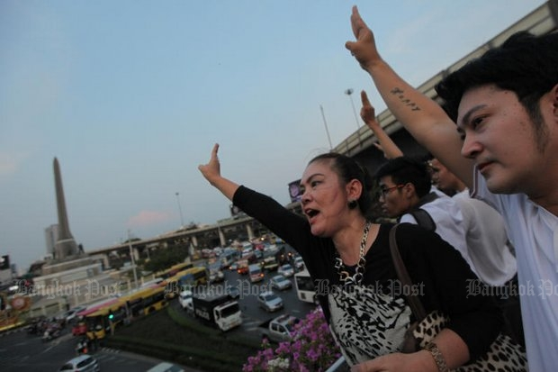 Four people claiming to be supporters of former MP Watana Muangsook give a three-finger salute during a brief gathering organised by anti-coup activists on the skywalk near Victory Monument. Anti-riot police broke up the demonstration, after the activists demanded the release of the politician who is being detained for defying the military regime's orders to adjust his attitude. (Photos by Wichan Charoenkiatpakul)